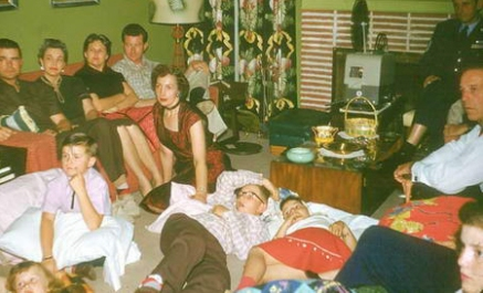 family sits in living room watching home moives in 1959