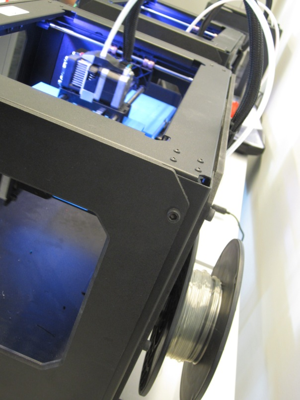 Spool of filament sits at the back of the printer.